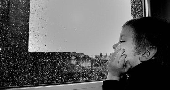 Nino-mirando-por-la-ventana-mientras-llueve_imagelarge